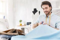 Funcionamento e sorriso masculinos inspirados da costureira Foto de Stock