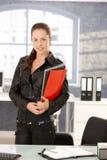 Funcionamento fêmea novo no sorriso do escritório fotografia de stock