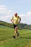 Funcionamento movimentando-se do homem mais idoso no prado Imagem de Stock Royalty Free