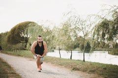 Funcionamento no parque Conceito ativo do esporte O desportista saudável faz exercícios na rua Atleta cansado no sportswear imagens de stock