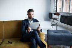 funcionamento O homem de negócios bem sucedido e elegante está usando uma tabuleta ao sentar-se no sofá no escritório moderno fotos de stock royalty free