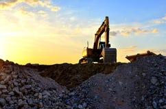 Funcionamento pesado da cubeta da máquina escavadora na pedreira em um fundo do por do sol e do céu azul Triturador de pedra da m fotos de stock