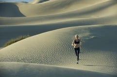 Funcionamentos da mulher em dunas de areia imagem de stock