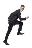 Funcionamentos do homem de negócios no terno preto no branco. Imagem de Stock