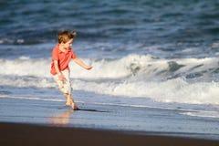Funcionamentos do miúdo na praia foto de stock