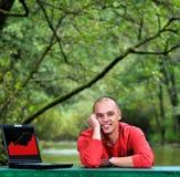 Funcionamiento al aire libre del hombre de negocios joven en la computadora portátil Fotografía de archivo libre de regalías