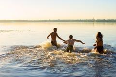 Funcionamiento alegre de los amigos en el agua en una nube del espray Imagen de archivo