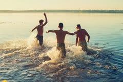Funcionamiento alegre de los amigos en el agua en una nube del espray Fotografía de archivo