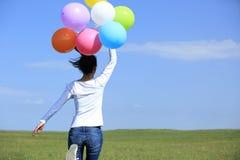 Funcionamiento asiático joven de la mujer con los globos coloreados Fotografía de archivo libre de regalías