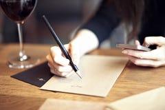 Funcionamiento caucásico joven de la mujer, escritura en un restaurante Concepto del asunto Disposiciones inmóviles Fotos de archivo