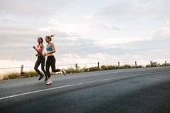 Funcionamiento de dos atletas de las mujeres imagen de archivo libre de regalías