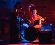 Funcionamiento de la banda de jazz Júntese de los músicos - batería y cantante en un club nocturno fotografía de archivo