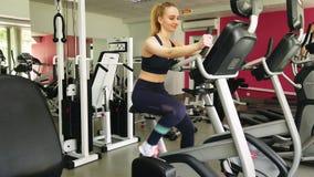 Funcionamiento de la chica joven en la bicicleta est?tica en el gimnasio del deporte