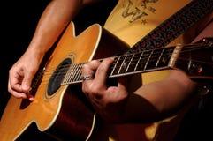 Funcionamiento de la guitarra acústica por la venda de la música Fotos de archivo libres de regalías