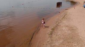 Funcionamiento de la madre y de la hija a lo largo del río a lo largo de la arena Playa D?a de verano asoleado Lanzamiento a?reo metrajes