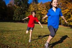 Funcionamiento de la muchacha y del muchacho, saltando en parque Fotos de archivo