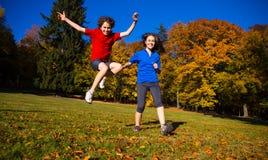 Funcionamiento de la muchacha y del muchacho, saltando en parque Imagen de archivo libre de regalías