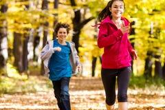Funcionamiento de la muchacha y del muchacho, saltando en parque Fotografía de archivo libre de regalías