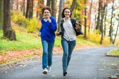 Funcionamiento de la muchacha y del muchacho, saltando en parque Fotografía de archivo