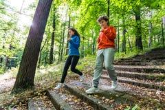Funcionamiento de la muchacha y del muchacho, saltando en parque Foto de archivo