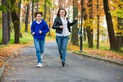 Funcionamiento de la muchacha y del muchacho, saltando en parque Imagen de archivo