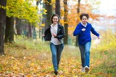 Funcionamiento de la muchacha y del muchacho, saltando en parque Imágenes de archivo libres de regalías