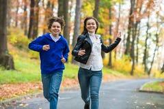 Funcionamiento de la muchacha y del muchacho, saltando en parque Imagenes de archivo