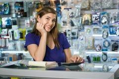 Funcionamiento de la mujer como dueño de tienda de informática que comprueba cuentas y facturas Foto de archivo libre de regalías