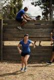 Funcionamiento de la mujer mientras que instructor que ayuda a hombres para subir una pared de madera Foto de archivo libre de regalías