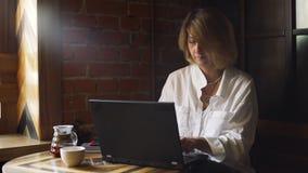 Funcionamiento de la mujer de negocios en el ordenador portátil en cafetería metrajes