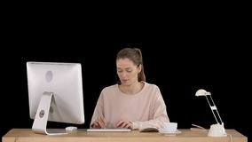 Funcionamiento de las auriculares de la mujer que lleva casual joven hermosa en el ordenador, Alpha Channel metrajes