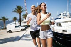 Funcionamiento de los pares Gente feliz que activa en la playa, resolviendo la sonrisa feliz fotos de archivo