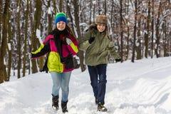 Funcionamiento del adolescente y de la muchacha al aire libre en parque del invierno Foto de archivo libre de regalías