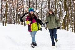 Funcionamiento del adolescente y de la muchacha al aire libre en parque del invierno Imagen de archivo libre de regalías