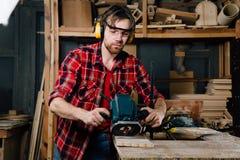 Funcionamiento del carpintero de la fresadora de la mano manual en el taller de la carpintería carpintero imagenes de archivo