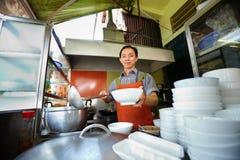 Funcionamiento del hombre como cocinero en cocina asiática del restaurante Fotos de archivo libres de regalías