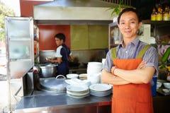 Funcionamiento del hombre como cocinero en cocina asiática del restaurante Imagen de archivo