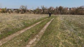 Funcionamiento del hombre con el perro blanco de la raza mezclada en un camino de tierra en la estación de primavera almacen de metraje de vídeo