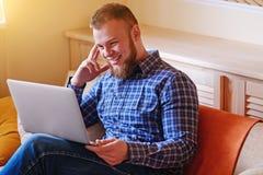 Funcionamiento del hombre joven absorbente en el ordenador portátil en casa fotos de archivo libres de regalías