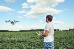 Funcionamiento del hombre joven del octocopter del abejón del vuelo en el campo verde Imagen de archivo libre de regalías