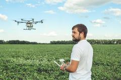 Funcionamiento del hombre joven del octocopter del abejón del vuelo en el campo verde Fotografía de archivo libre de regalías
