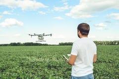Funcionamiento del hombre joven del octocopter del abejón del vuelo en el campo verde Imagen de archivo