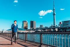 Funcionamiento del hombre por el río de Sumida, Tokio Skytree en fondo Entrenamiento del deporte, forma de vida sana, o Tokio con fotografía de archivo