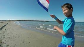 Funcionamiento del muchacho a lo largo de la playa con la bandera almacen de metraje de vídeo