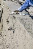 Funcionamiento del trabajador de construcci?n de la piscina con el flotador de madera en el hormig?n mojado imagenes de archivo
