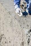Funcionamiento del trabajador de construcci?n de la piscina con el flotador de madera en el hormig?n mojado imagen de archivo