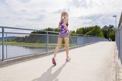 Funcionamiento delgado de la mujer al aire libre en el puente sobre un lago Foto de archivo