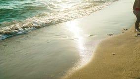 Funcionamiento desnudo y descalzo del niño a lo largo de la playa en un día de verano de la puesta del sol 4k almacen de video