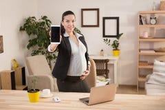 Funcionamiento embarazada de la mujer de negocios Imagen de archivo libre de regalías