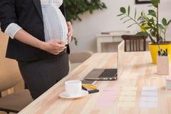 Funcionamiento embarazada de la mujer de negocios Fotos de archivo libres de regalías